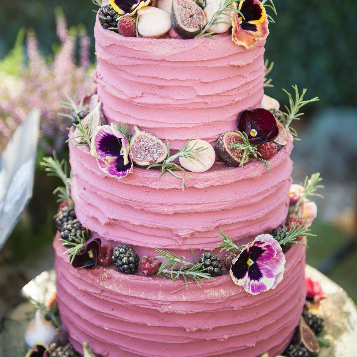 A pink wedding cake with berries and figs