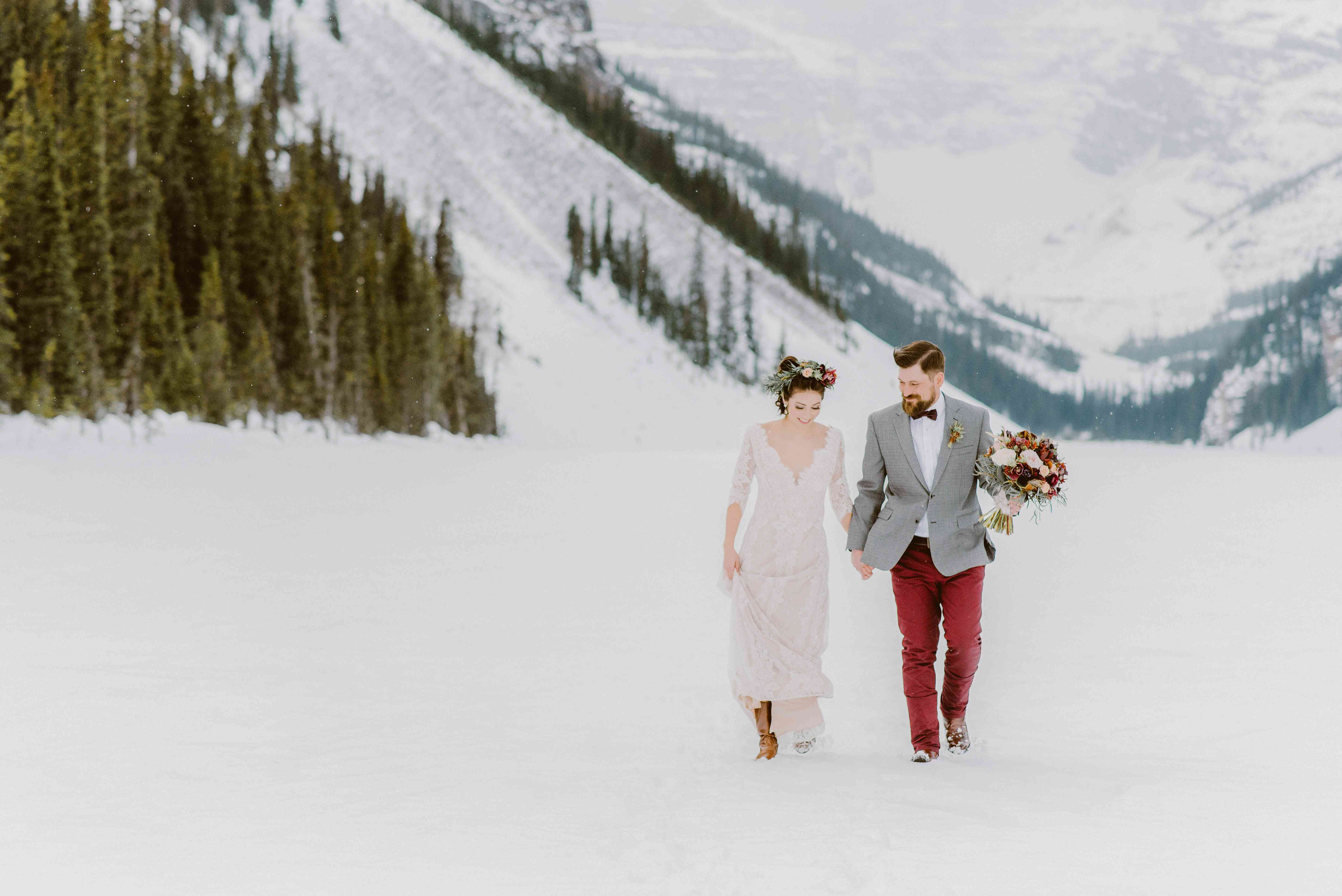 Bride and groom hand in hand walking through a snowy field with mountains in the background