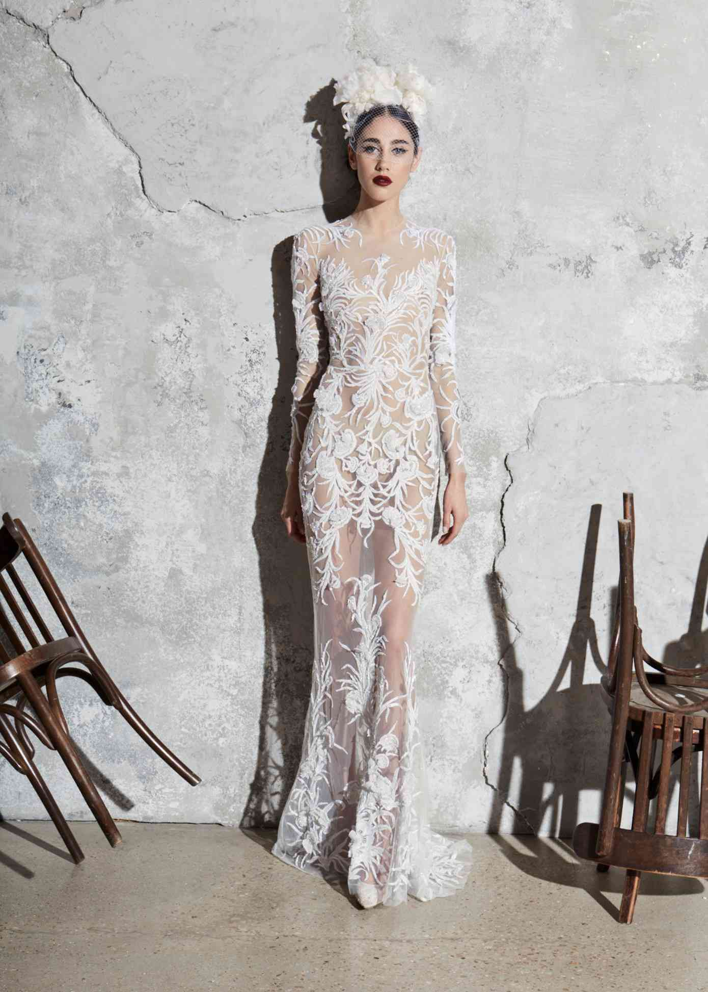 Model in an allover illusion tulle long-sleeve sheath gown with beaded embroidery and floral appliques