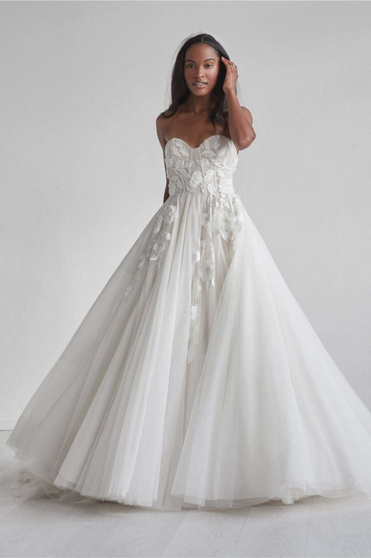 Model in strapless ballgown with floral embellishments and a tulle skirt