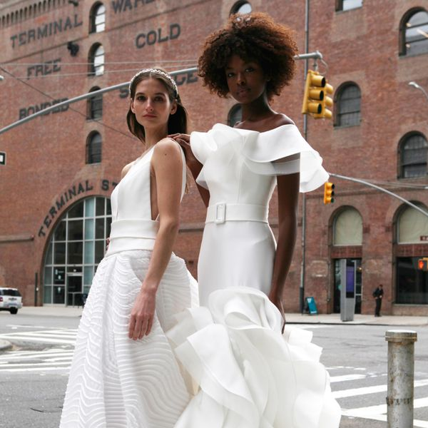 Two models in Valentini Spose wedding gowns in street.