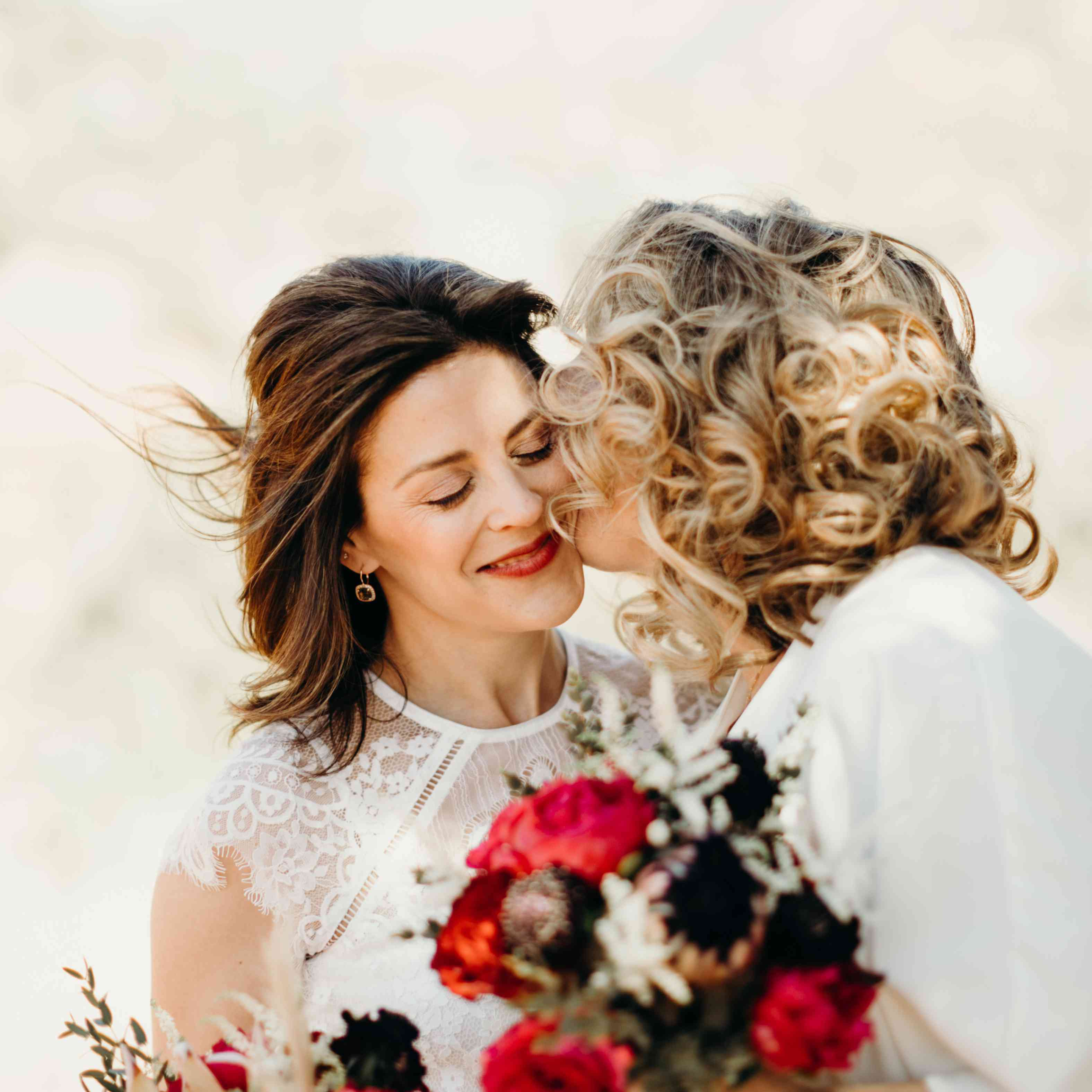 <p>kiss on the cheek two brides</p>