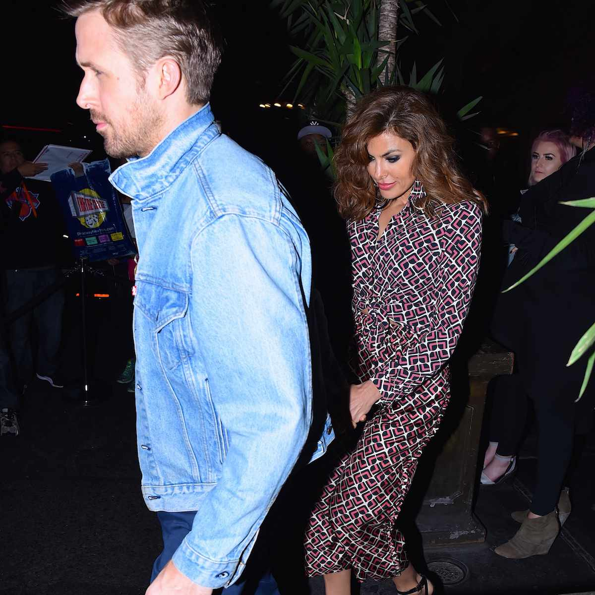 A side-profile shot of Ryan Gosing in a denim jacket with wife Eva Mendes in tow in a printed dress