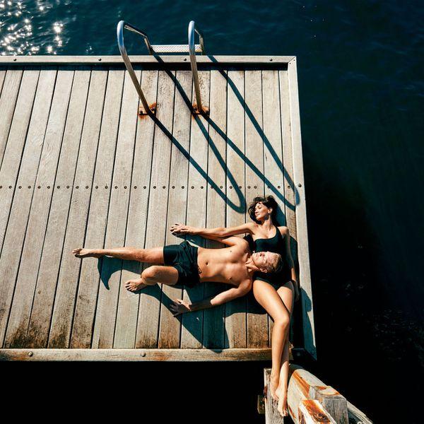couple sunbathing on dock