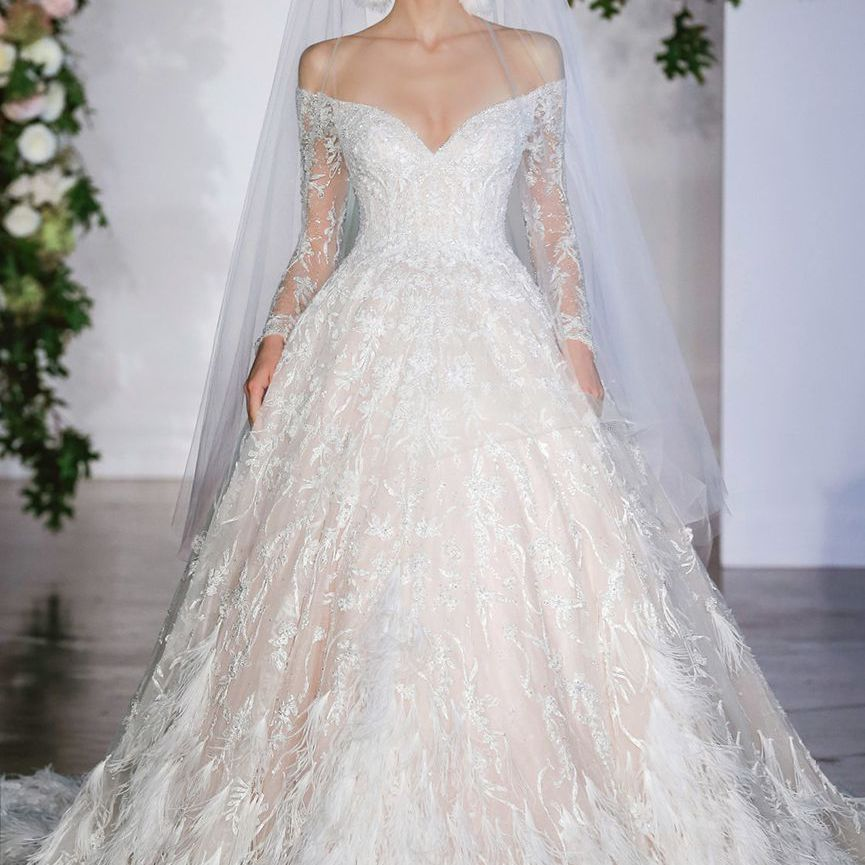 Model in long sleeve off-the-shoulder ballgown with floral embroidery and feather trim