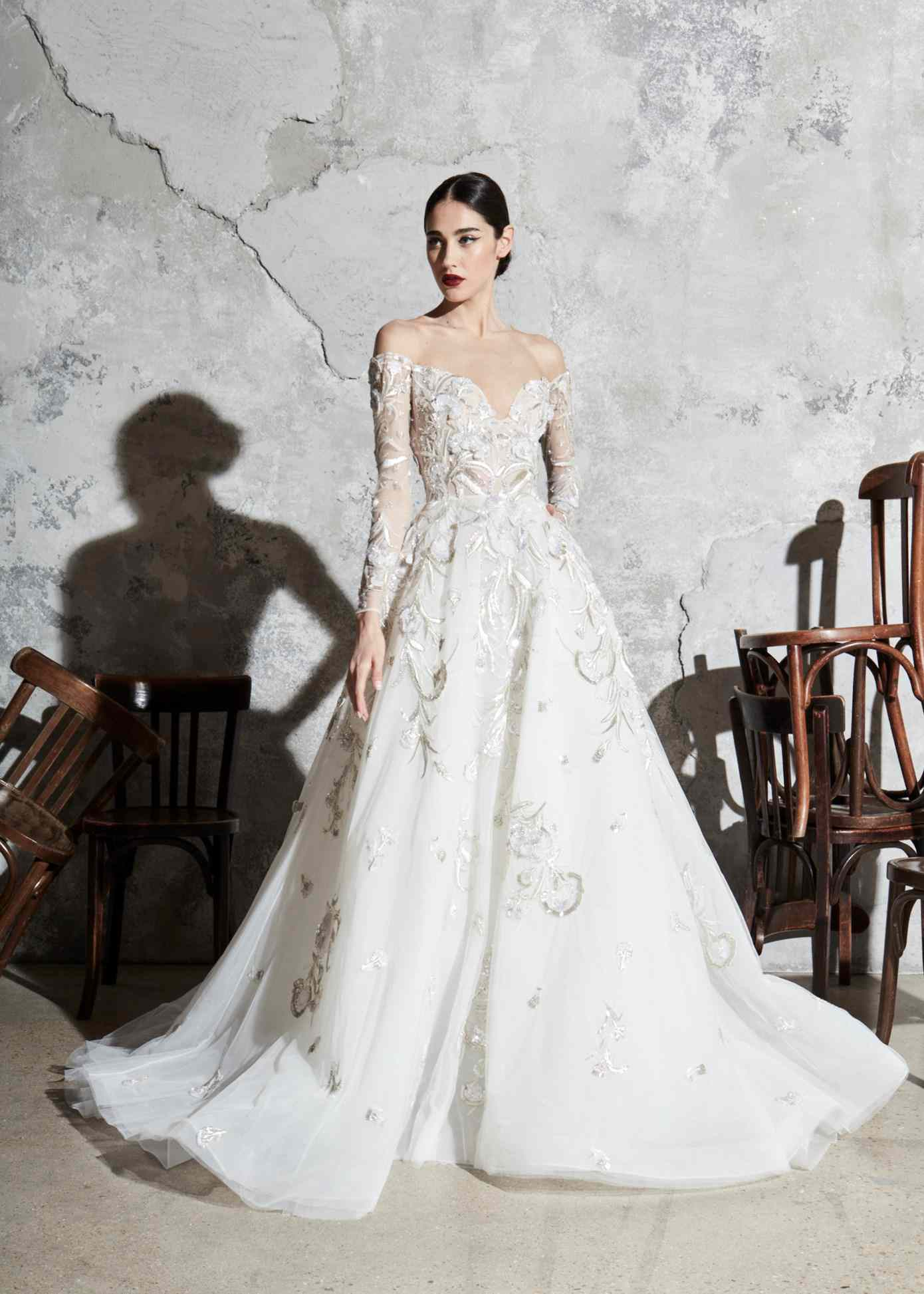 Model in off-the-shoulder long-sleeve ballgown with deep sweetheart neckline and silver and gold embroidery