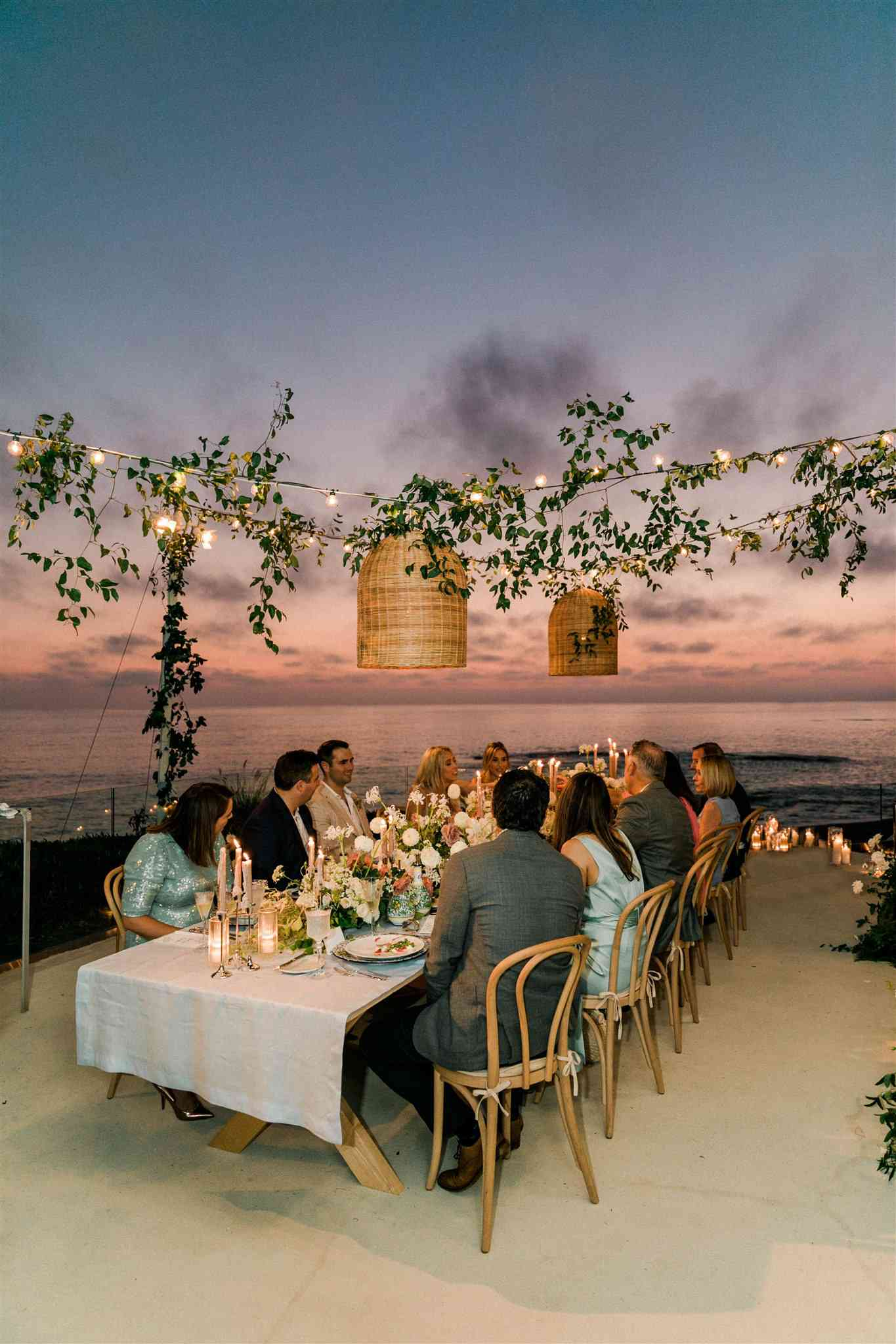 Guests at a wedding sitting at a reception table by the beach at sunset