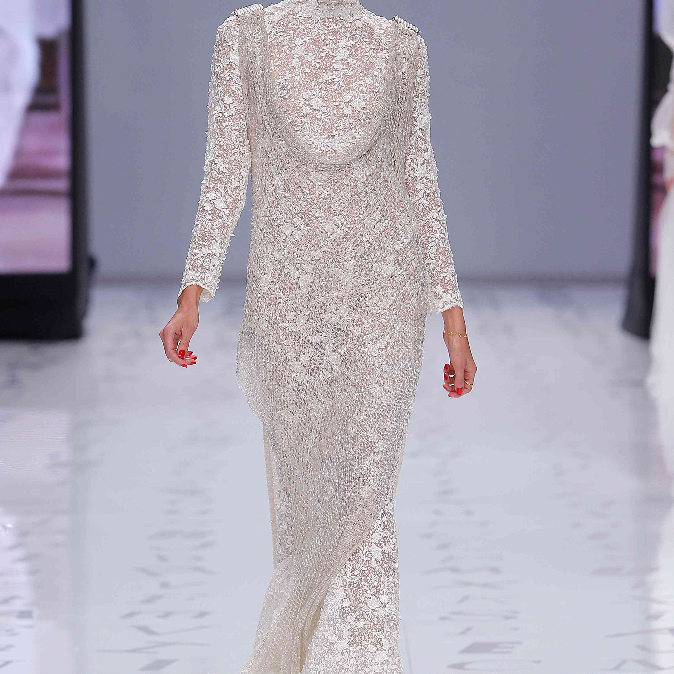 Model in a long-sleeve mock-neck lace mermaid dress with a sleeveless scoop-neck mesh overlay