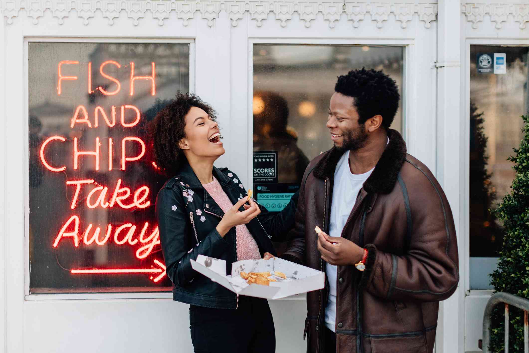 Couple eating outside a fish and chips restaurant