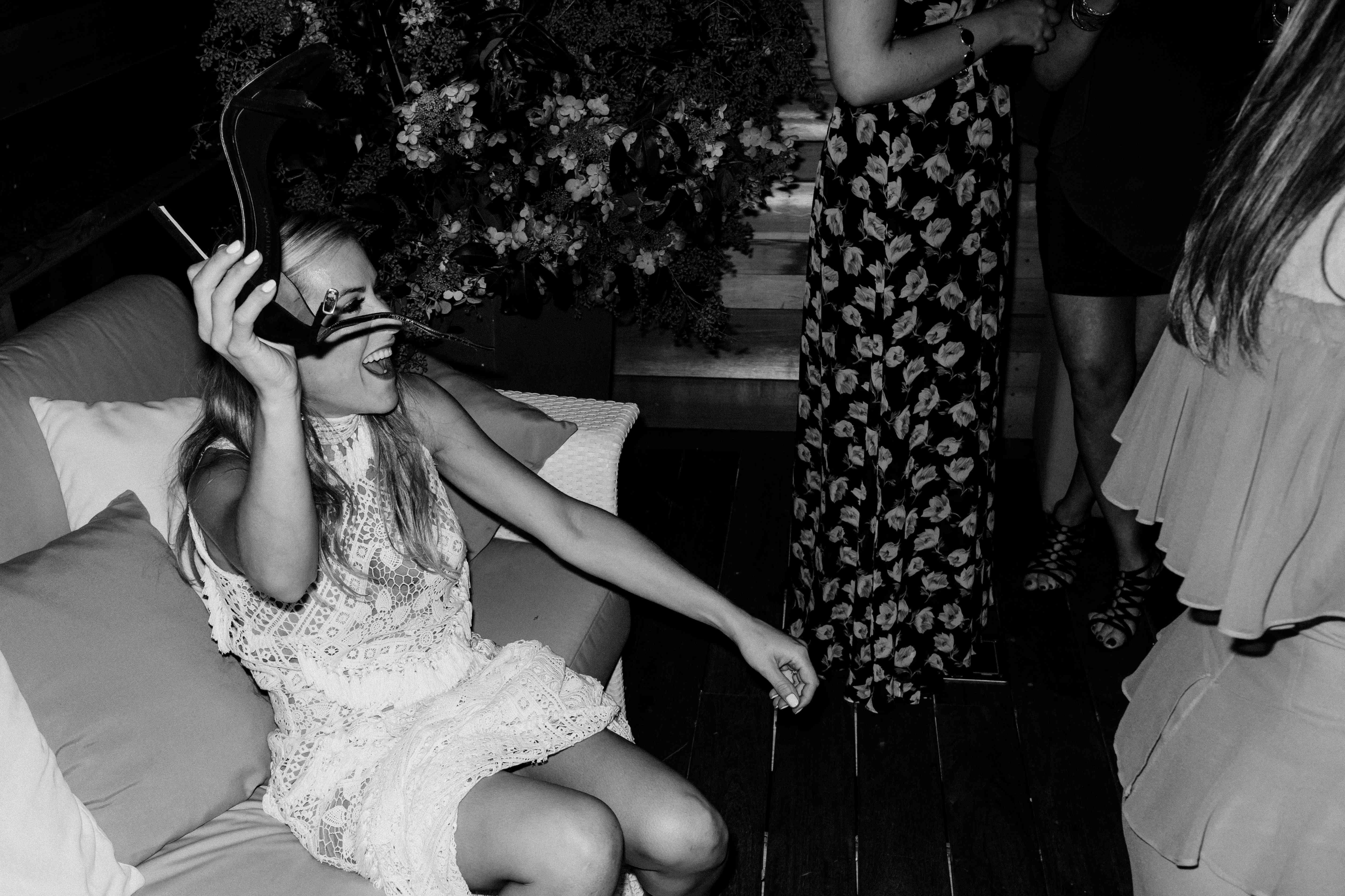 Bride holding shoe dancing