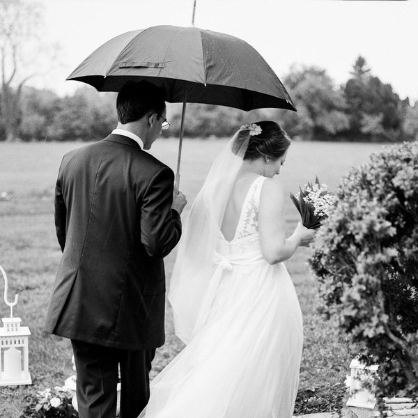 Bride and groom holding an umbrella