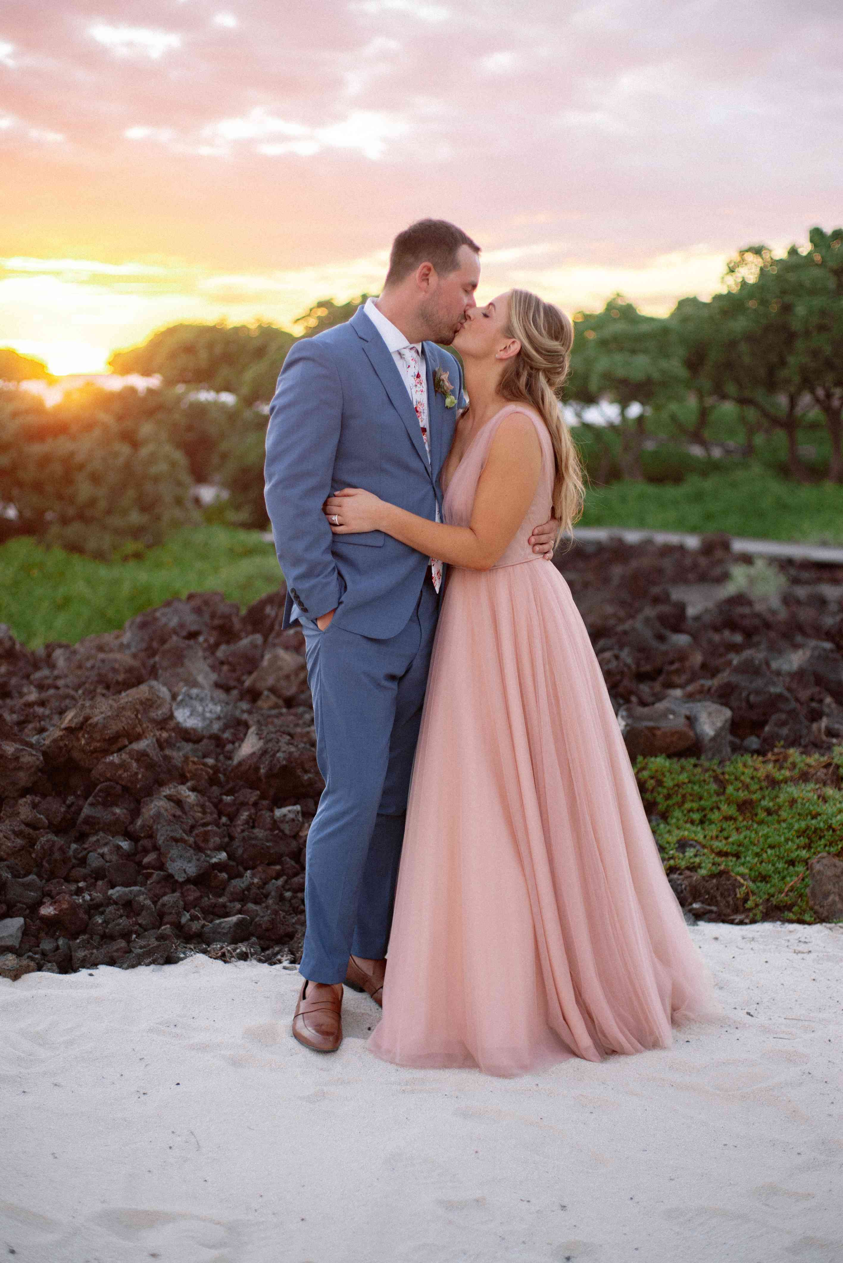 The couple kisses at sunset