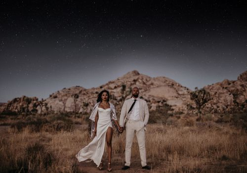 Wedding couple standing in front of mountains under starry sky