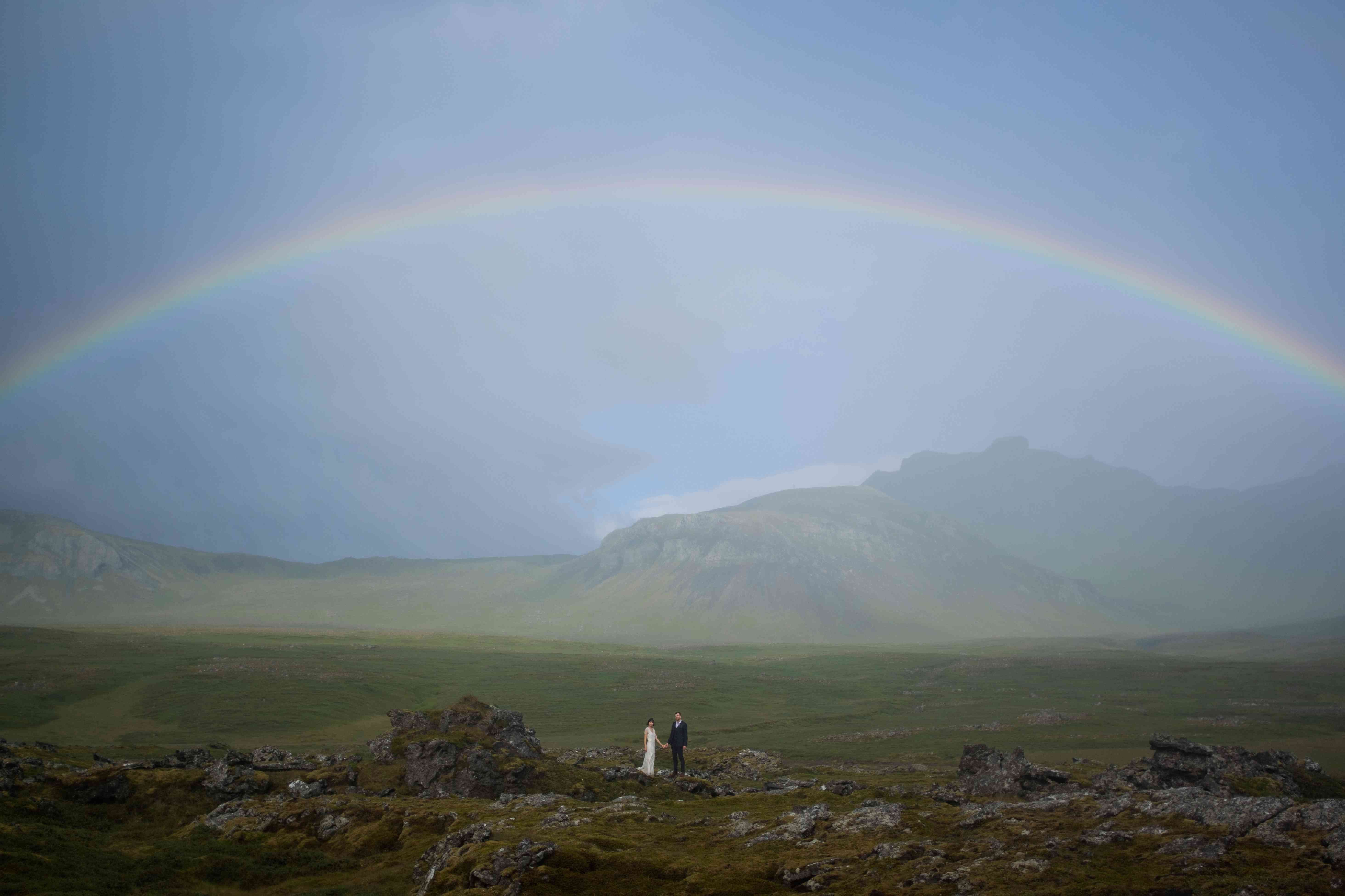 Couple holding hands under a rainbow in Iceland