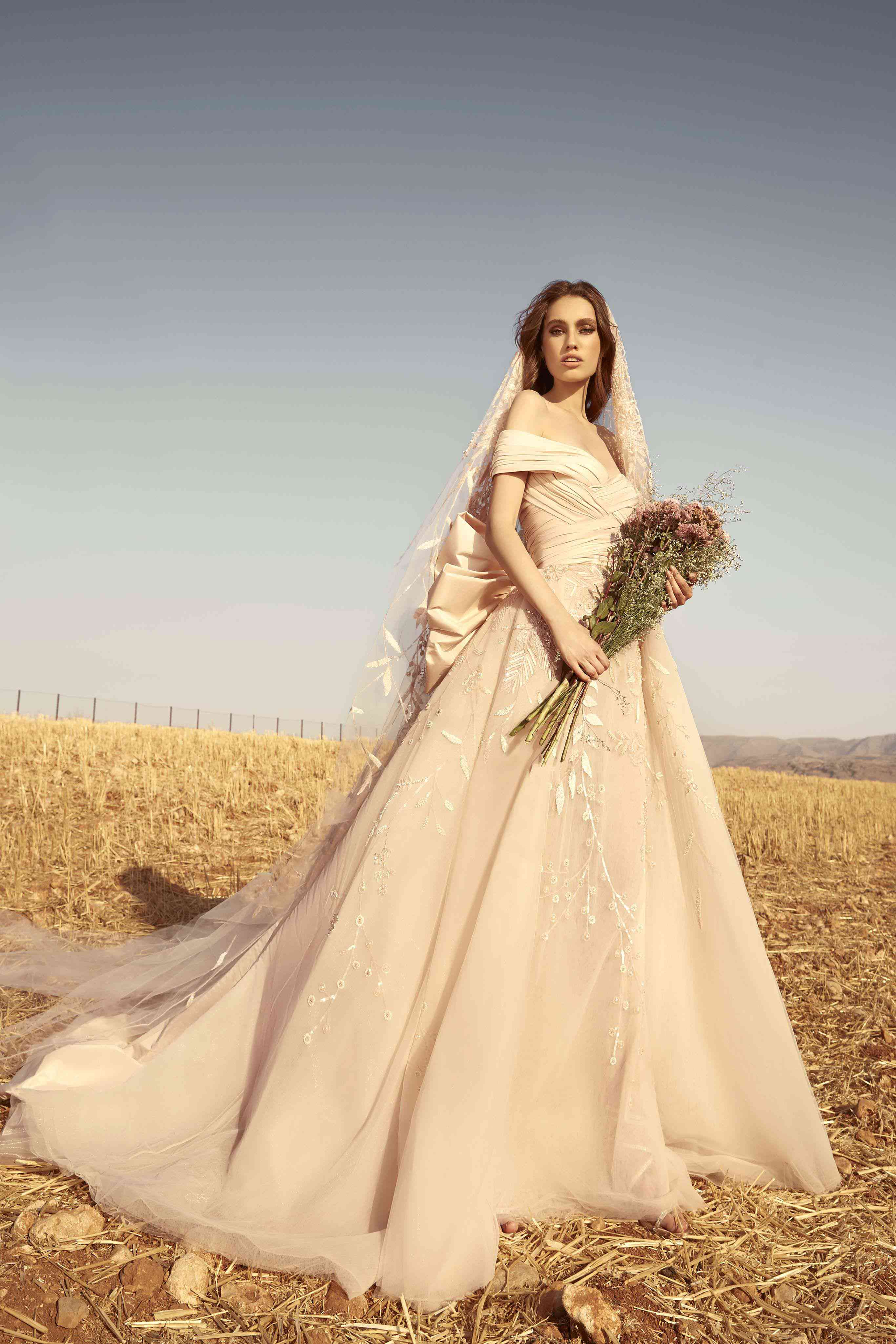 Model in a draped off-shoulder shell taffeta dress with an embroidered tulle skirt and matching veil