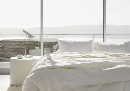 Bed with off-white covers in room with large windows