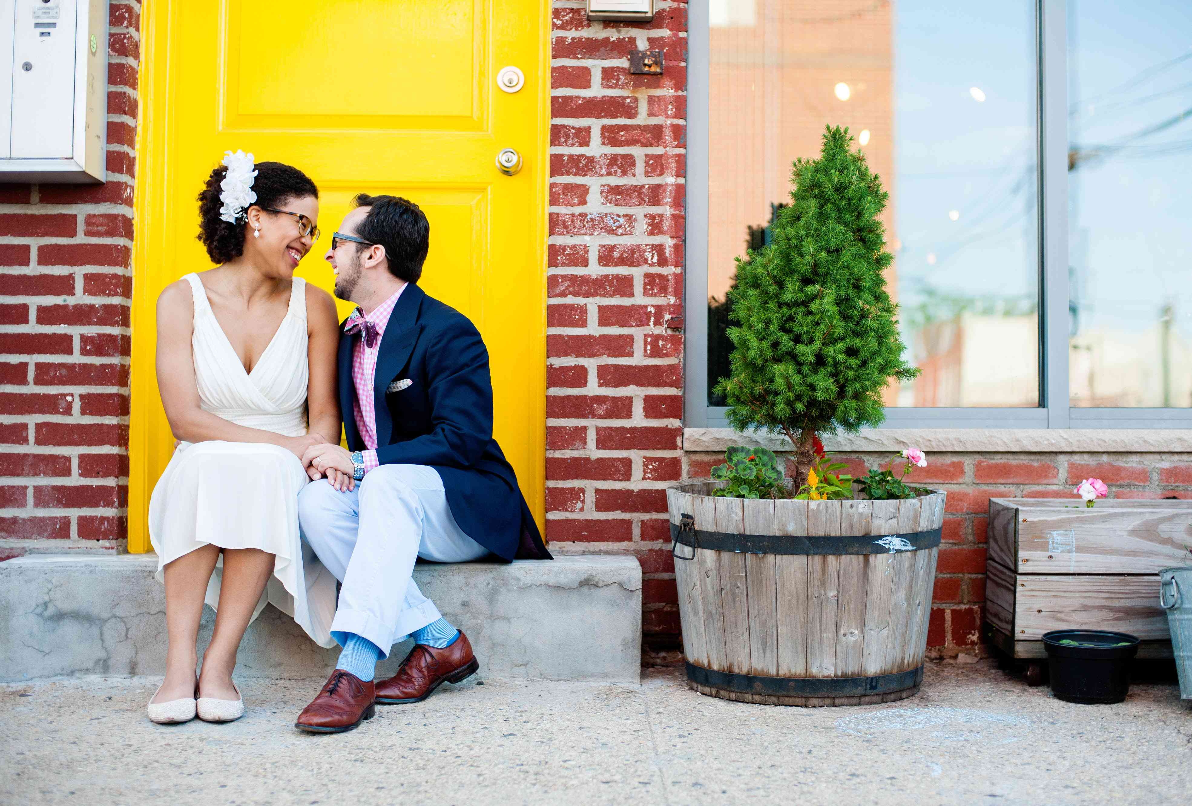 Bride and groom sitting on stoop and looking at each other happily