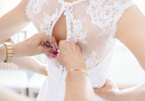 <p>Bride Putting On Her Wedding Dress</p>