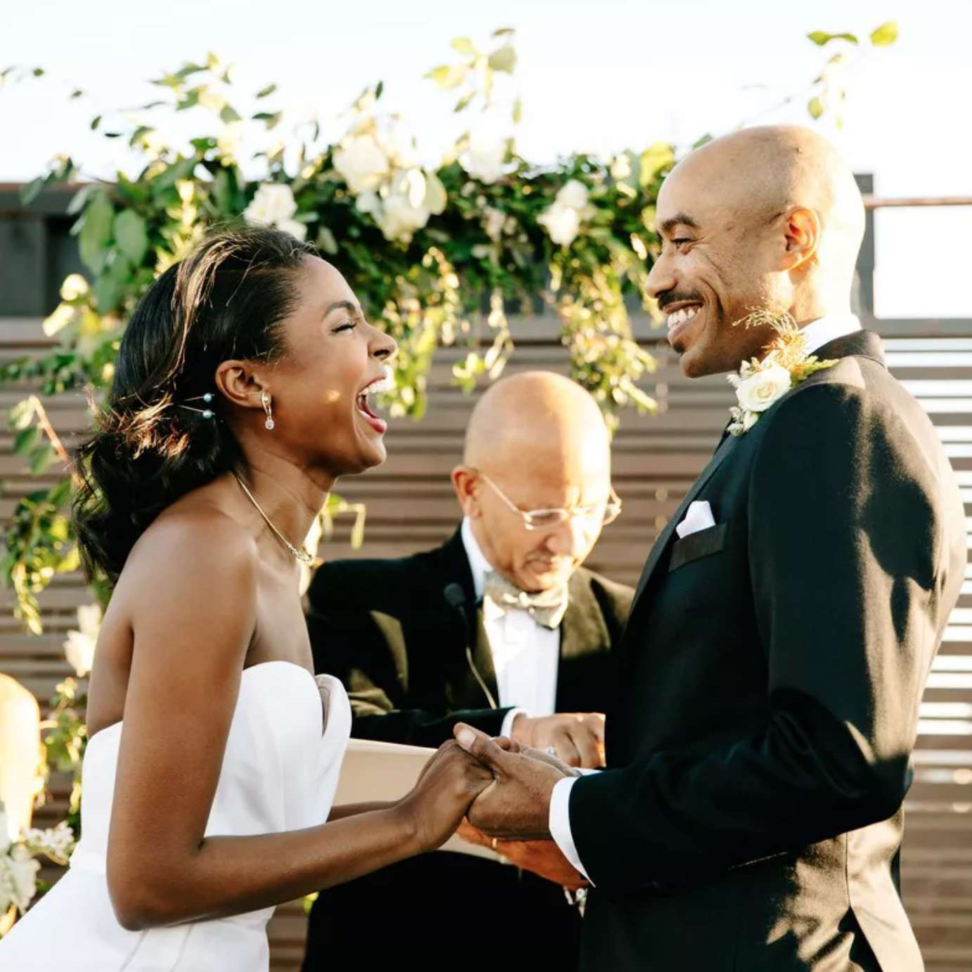 Newlyweds laughing during vow exchange