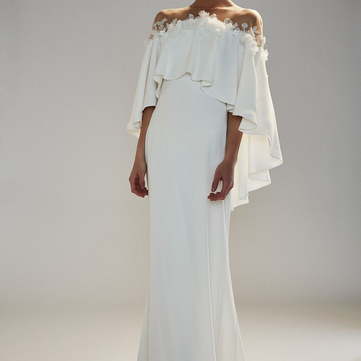 Model in off-the-shoulder crepe gown with cascading ruffle and floral applique