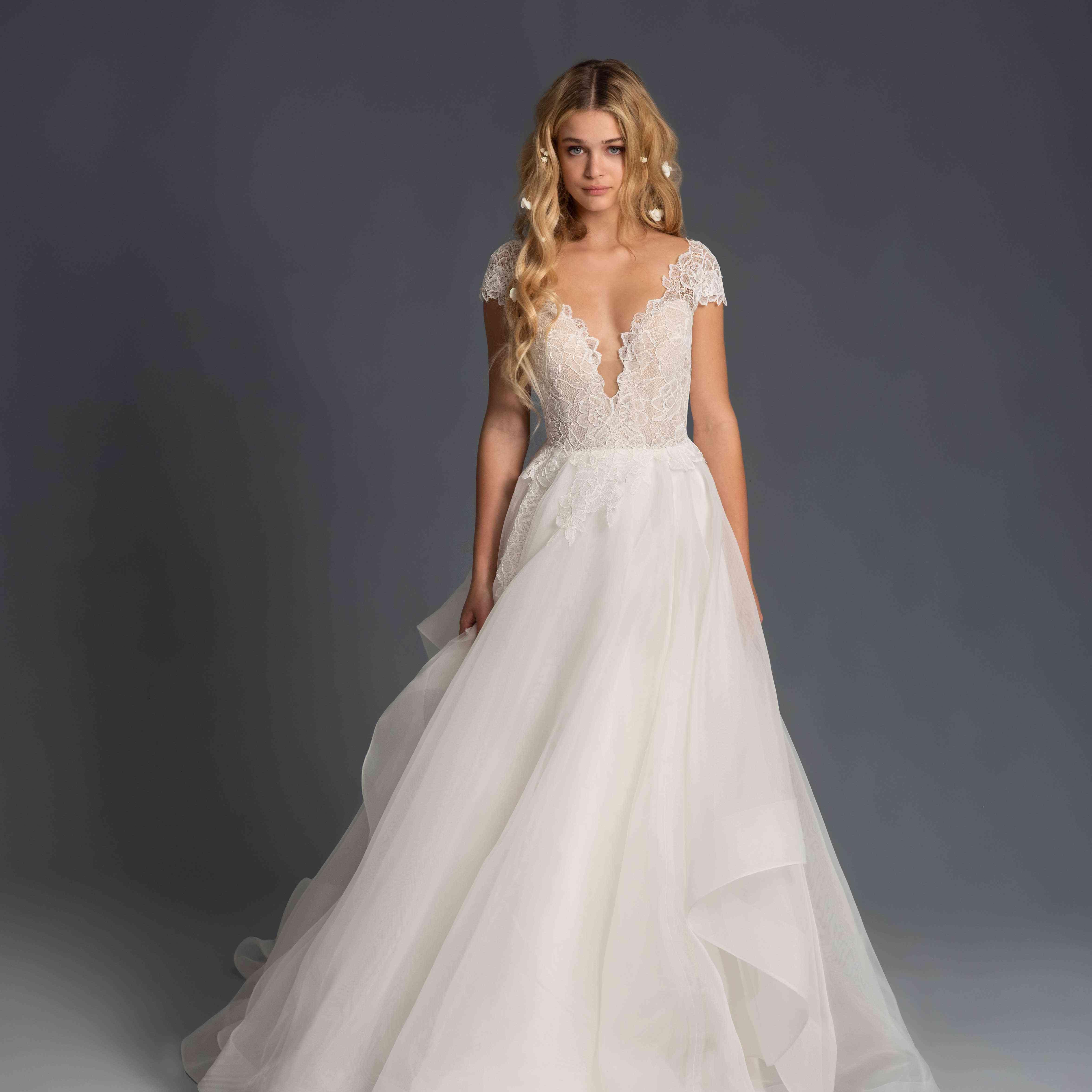 Model in cap sleeve plunging wedding dress