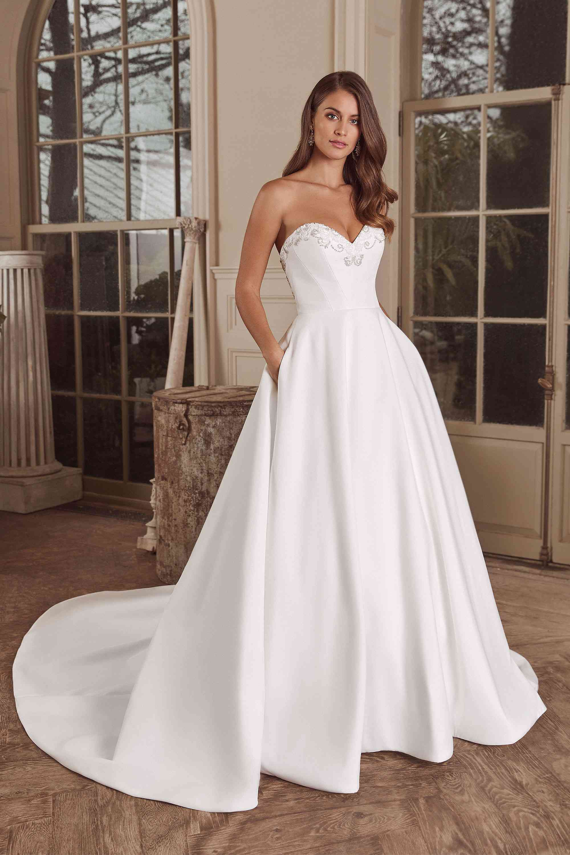 Model in white ball gown with beaded sweetheart neckline and skirt pockets
