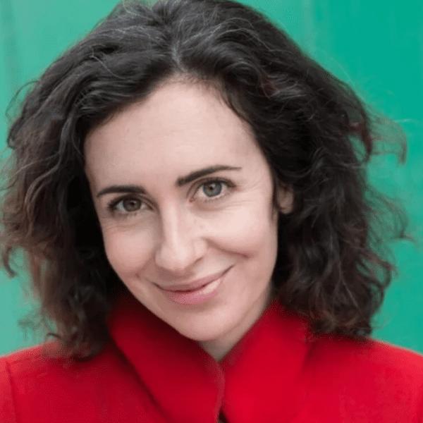 Una LaMarche headshot, wearing red coat against green background