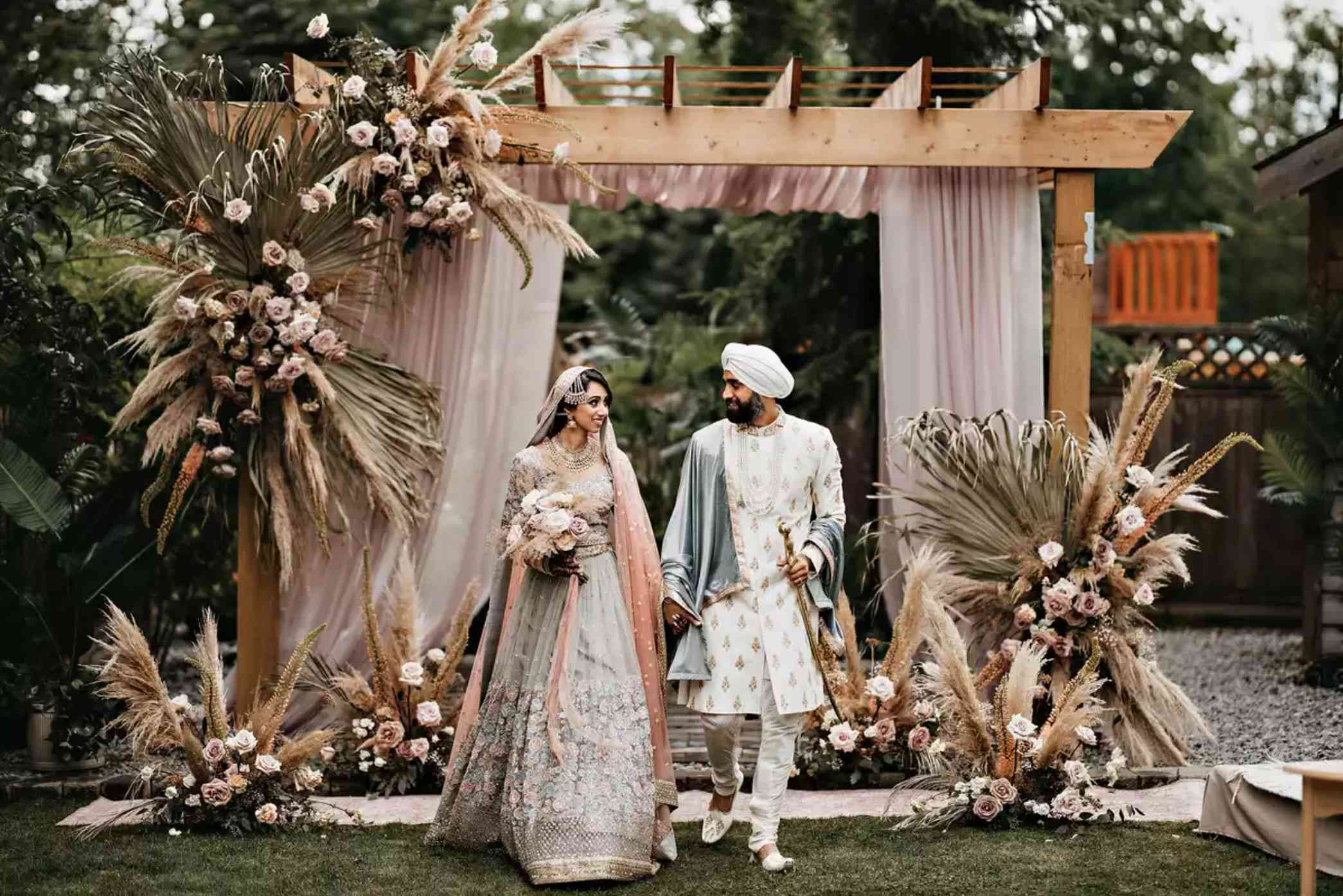 Newlyweds in front of wedding arch with pampas grass, dried palm leaves, and roses