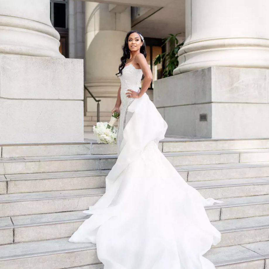 Bride showing off long train on stairs
