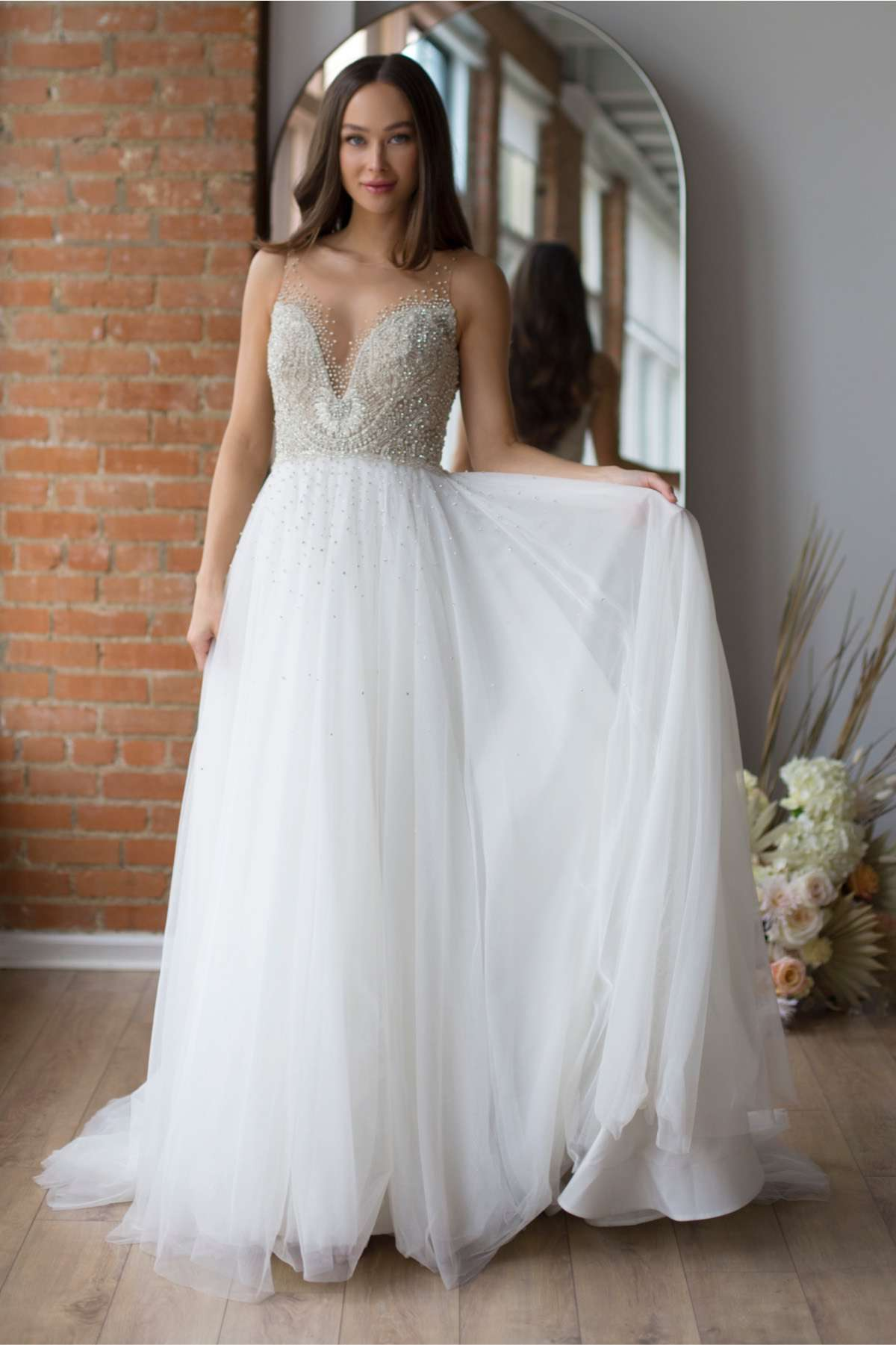 Model in A-line wedding gown with an allover beaded bodice and a soft net skirt