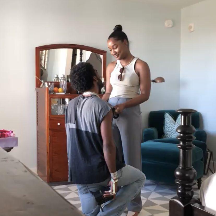 man on bended knee proposing to girlfriend