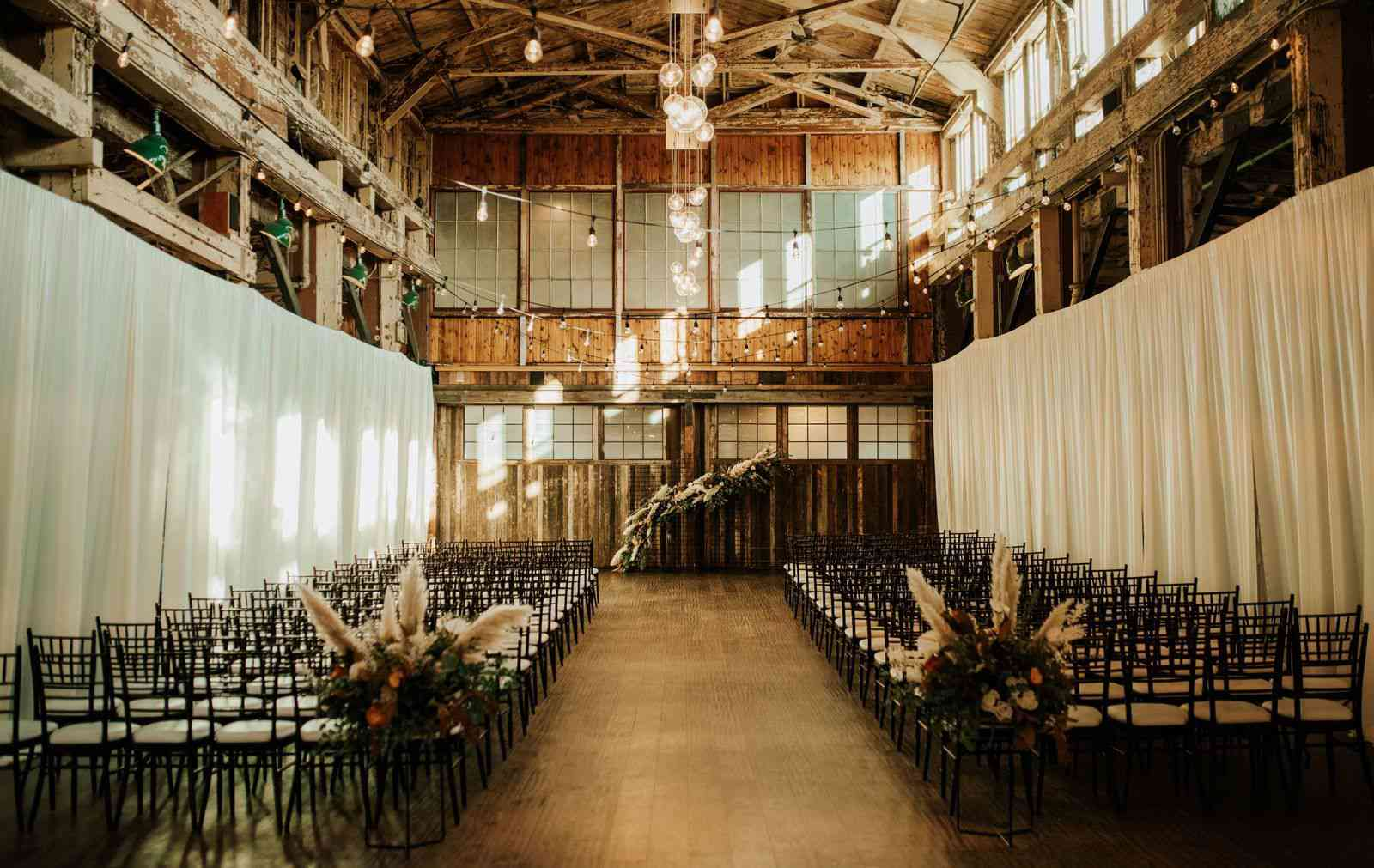 An indoor ceremony with floral installations at the start of the aisle to match the arch backdrop