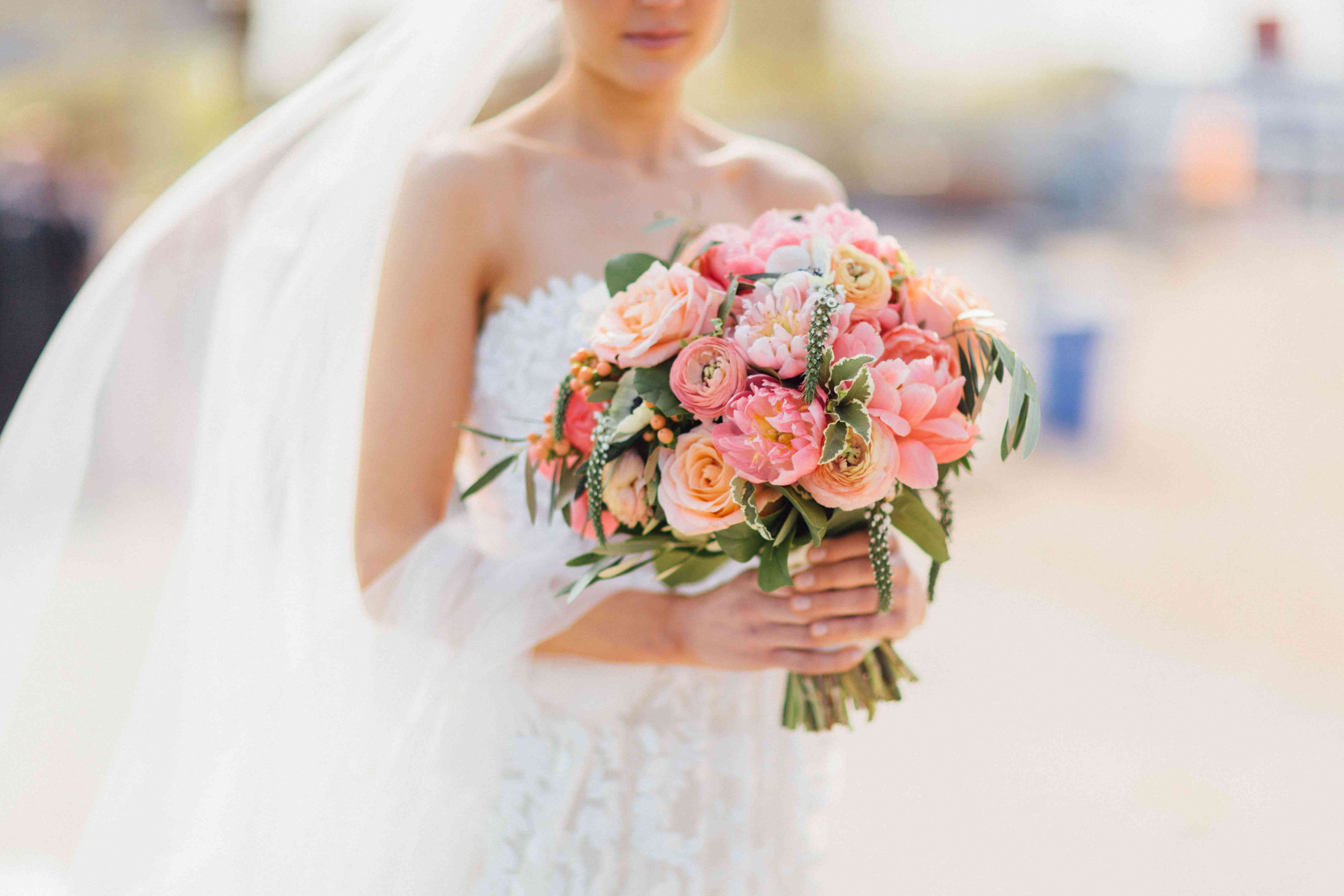 Bride holding a peach and coral bouquet
