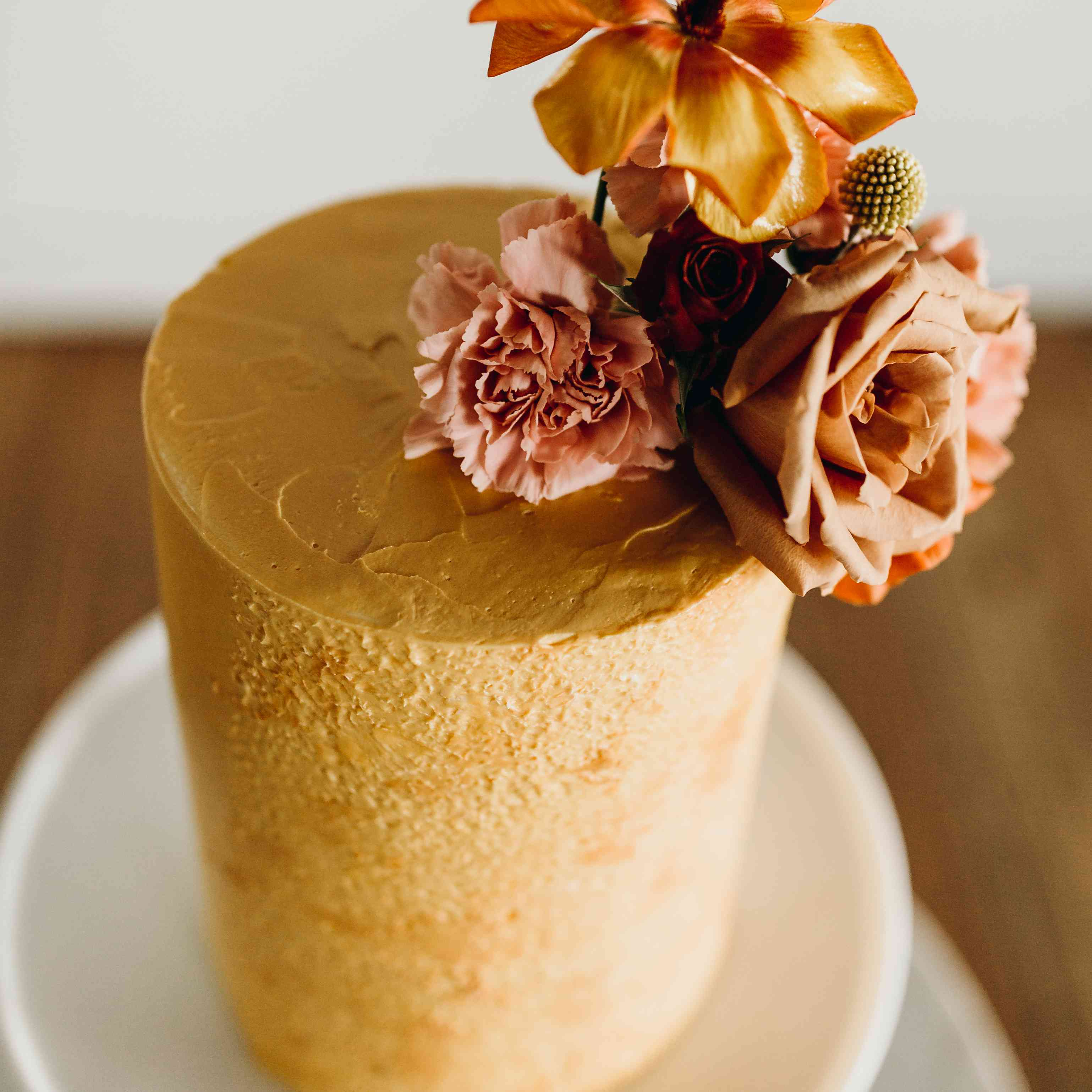 Single tier burnt orange cake with floral accents