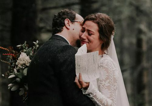 Groom kissing bride on cheek as she gets emotional holding handwritten vows