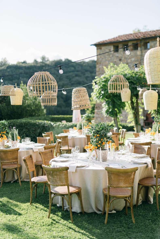 Outdoor wedding reception with hanging wicker lanterns