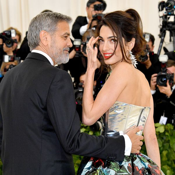 George Clooney places his hand on the small of wife Amal's back as she smiles and brushes a strand of hair off her face.