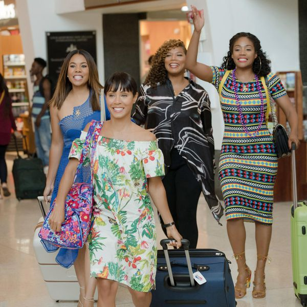 Four smiling women walking through an airport with luggage
