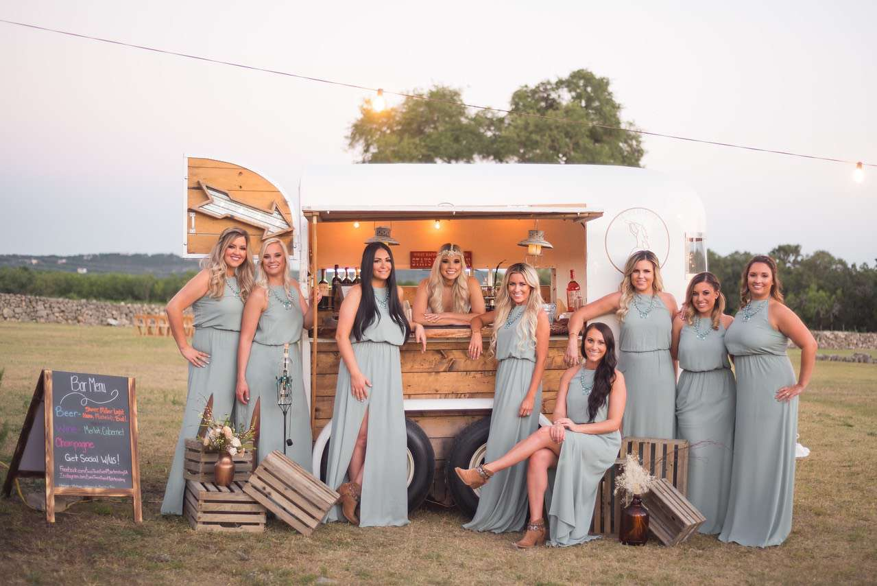 Bridesmaids in slate blue bridesmaid dresses standing in front of mobile bar under strings of lights at outdoor rustic wedding