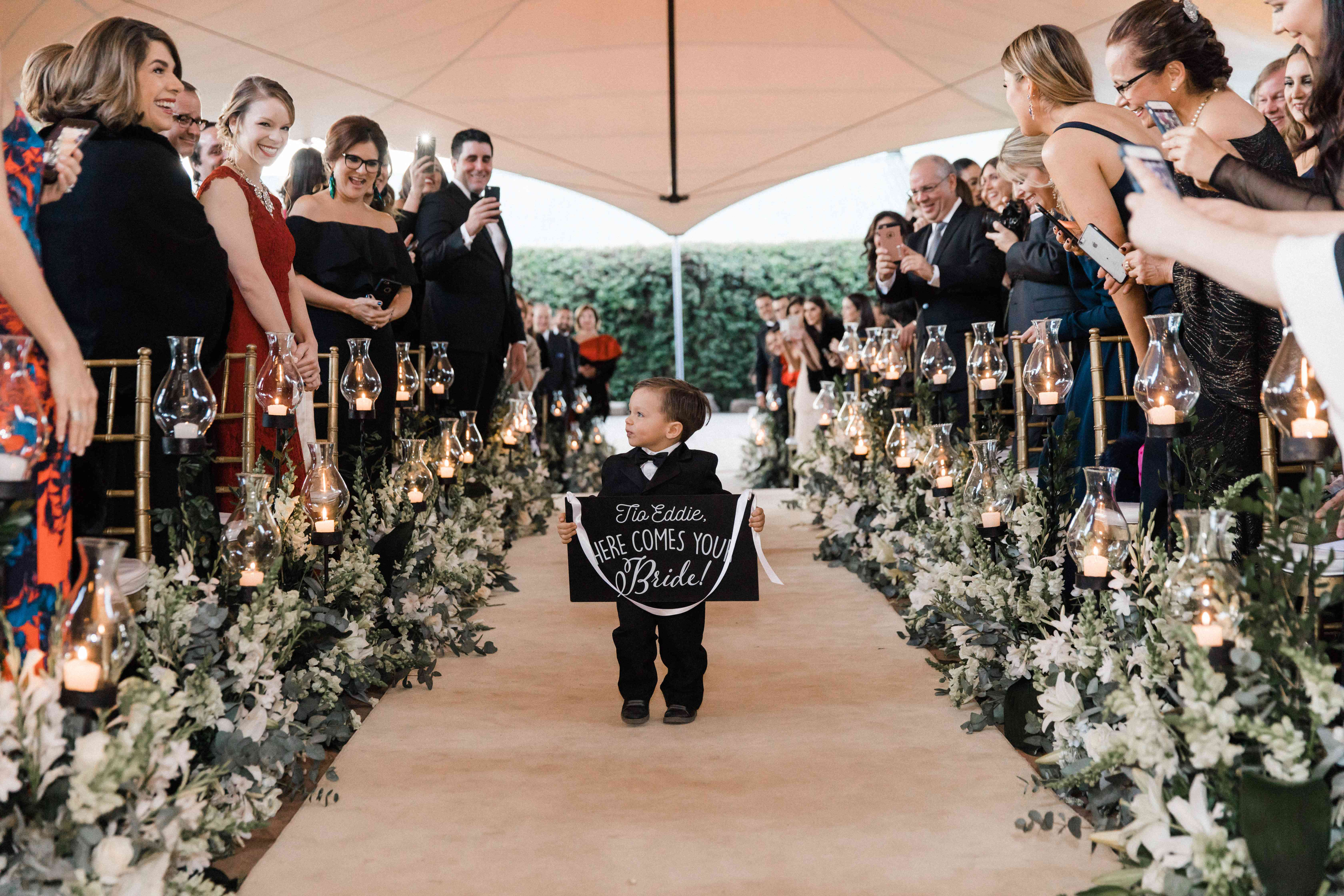 <p>ring bearer with sign walking down candle lined aisle</p><br><br>