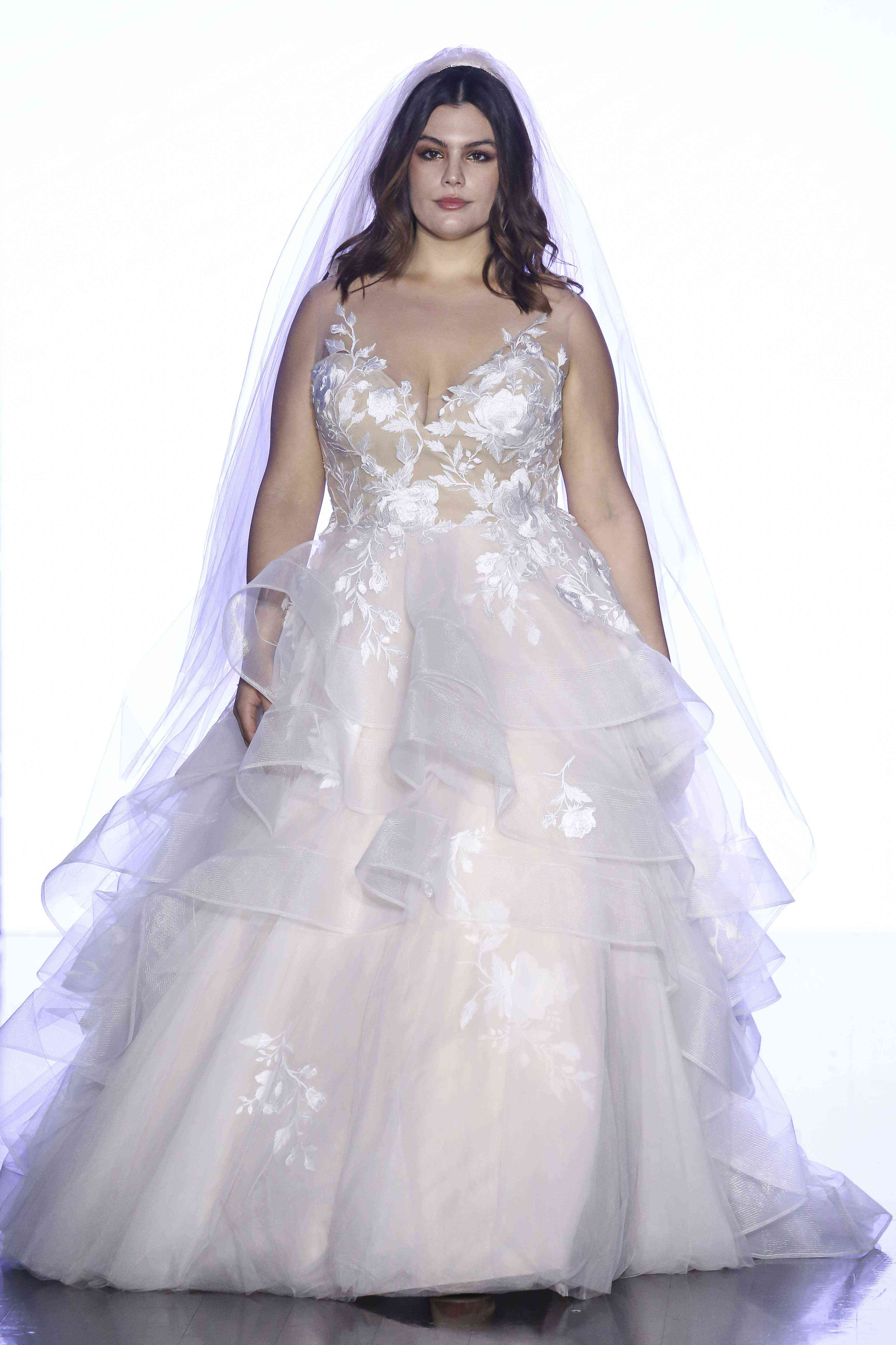 Model in ballgown with floral embroidered illusion V-neck bodice and a layered embroidered tulle skirt