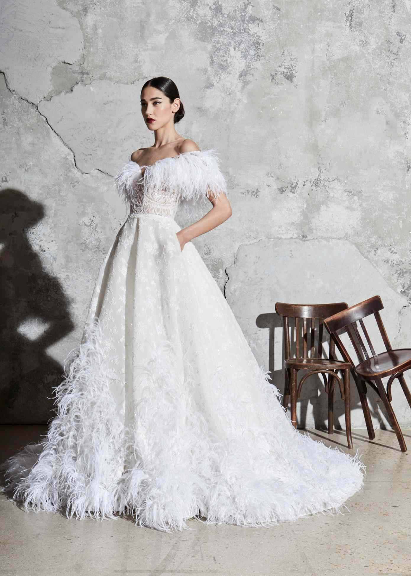 Model in off-the-shoulder ballgown with ostrich feather detail on the neckline, an embroidered bodice, and a floral skirt with ostrich feather detail on the hemline