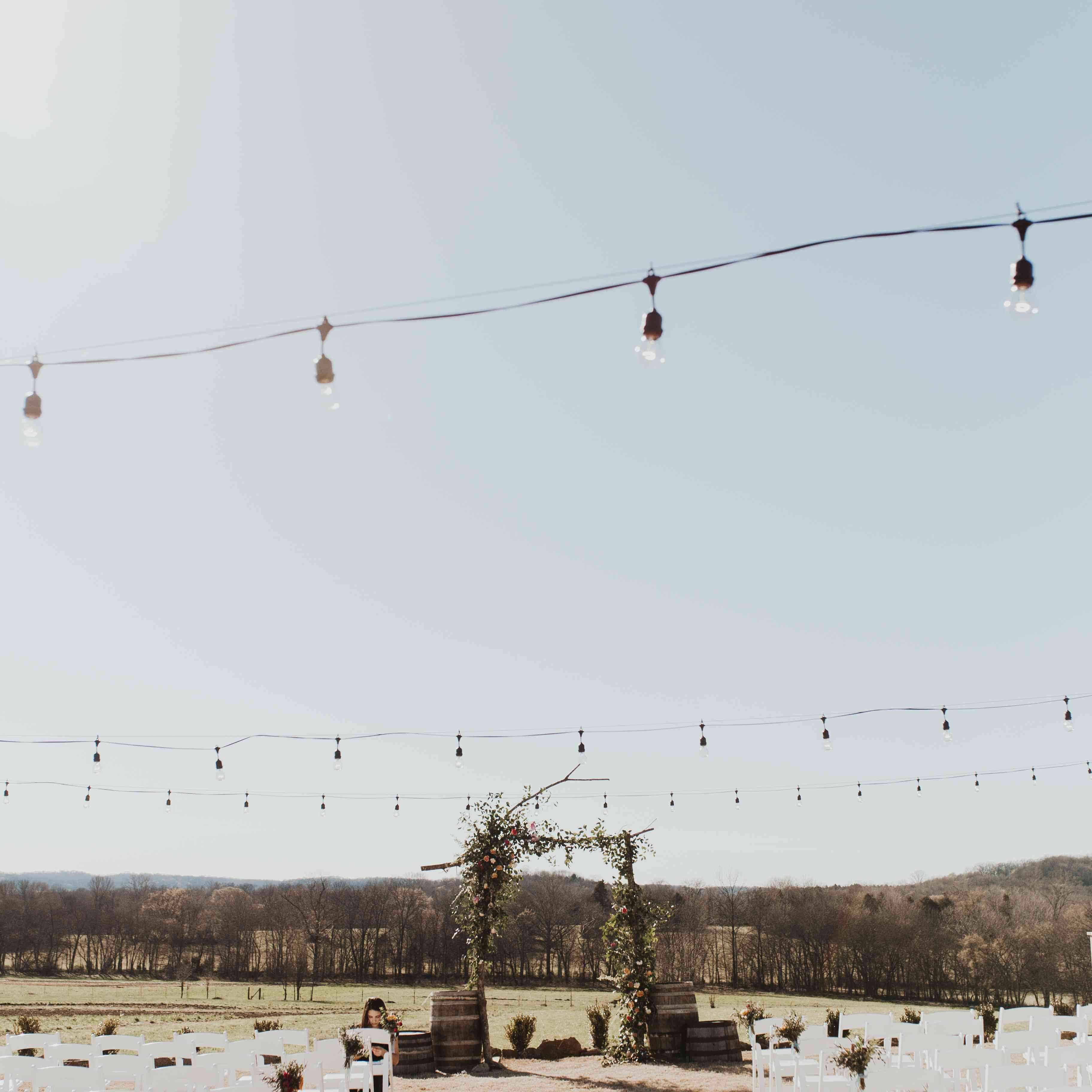 Outdoor ceremony with string lights over aisle and branch arch with barrels on each side