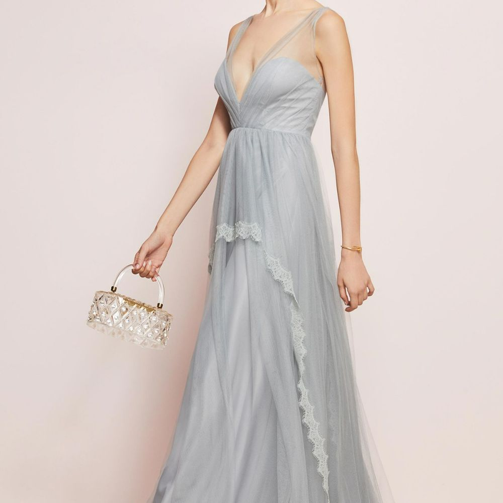 Model in a light blue, wispy V-neck gown with lace trim along the skirt