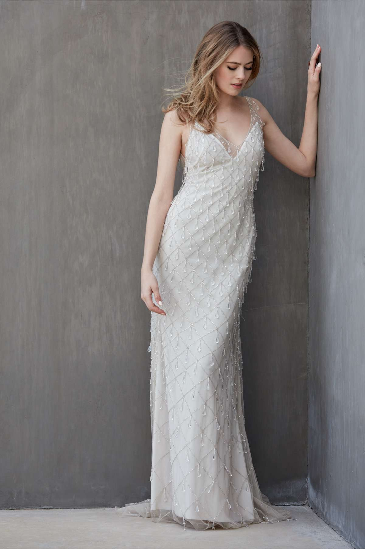Model in sleeveless V-neck sheath gown with diamante drop crystals in a lattice pattern