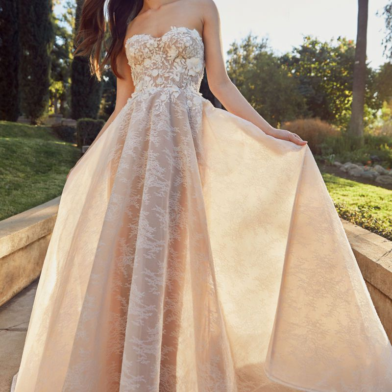 Model in strapless floral lace ball gown