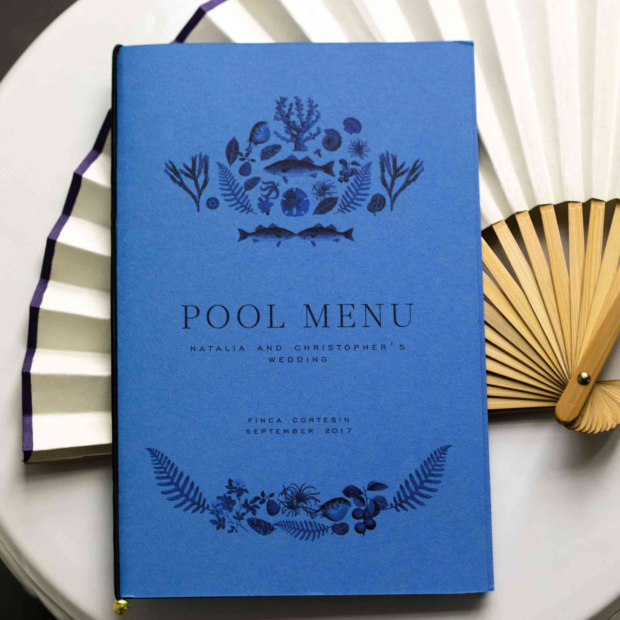 blue wedding reception menu and paper fan