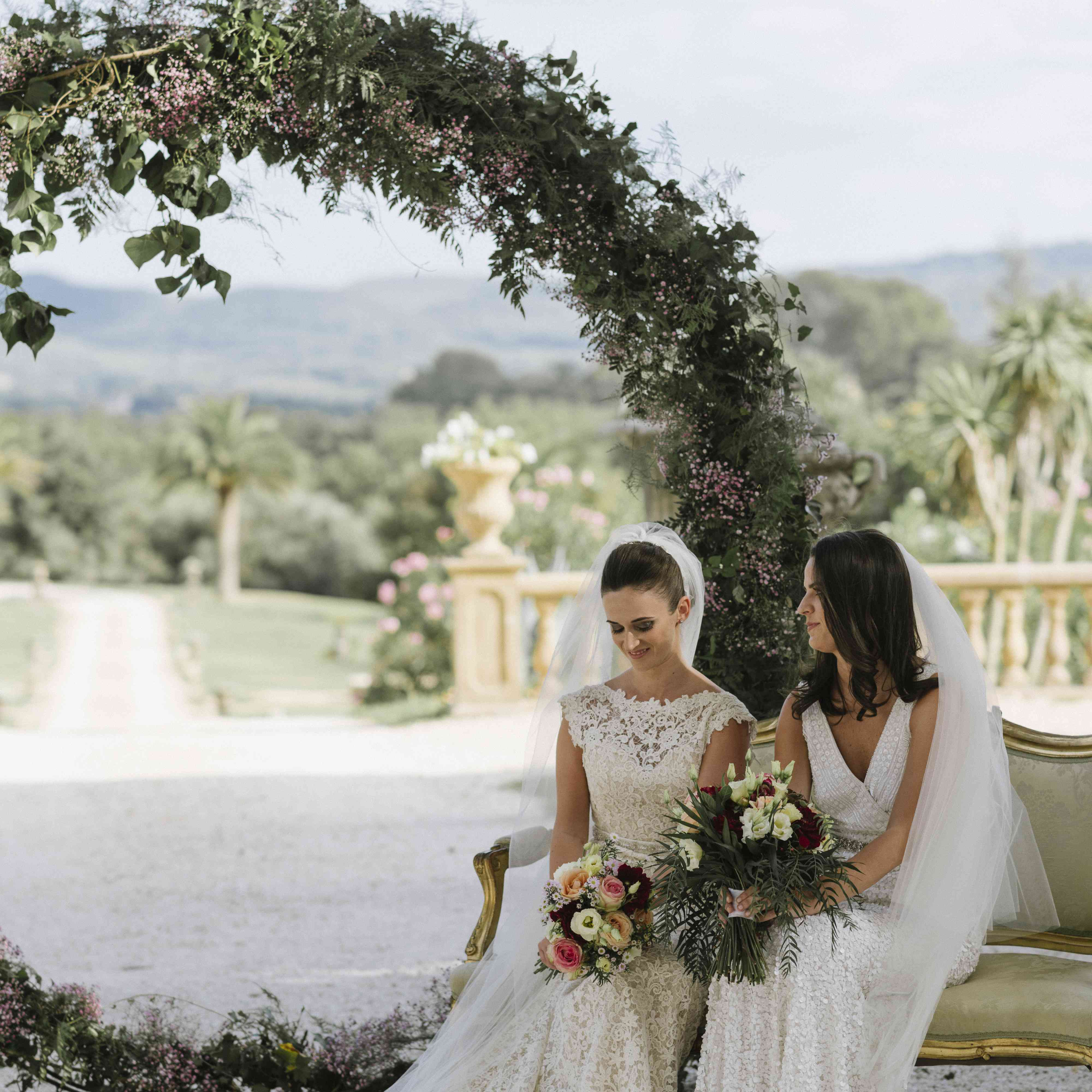 <p>brides sitting on couch outdoor wedding ceremony</p><br><br>