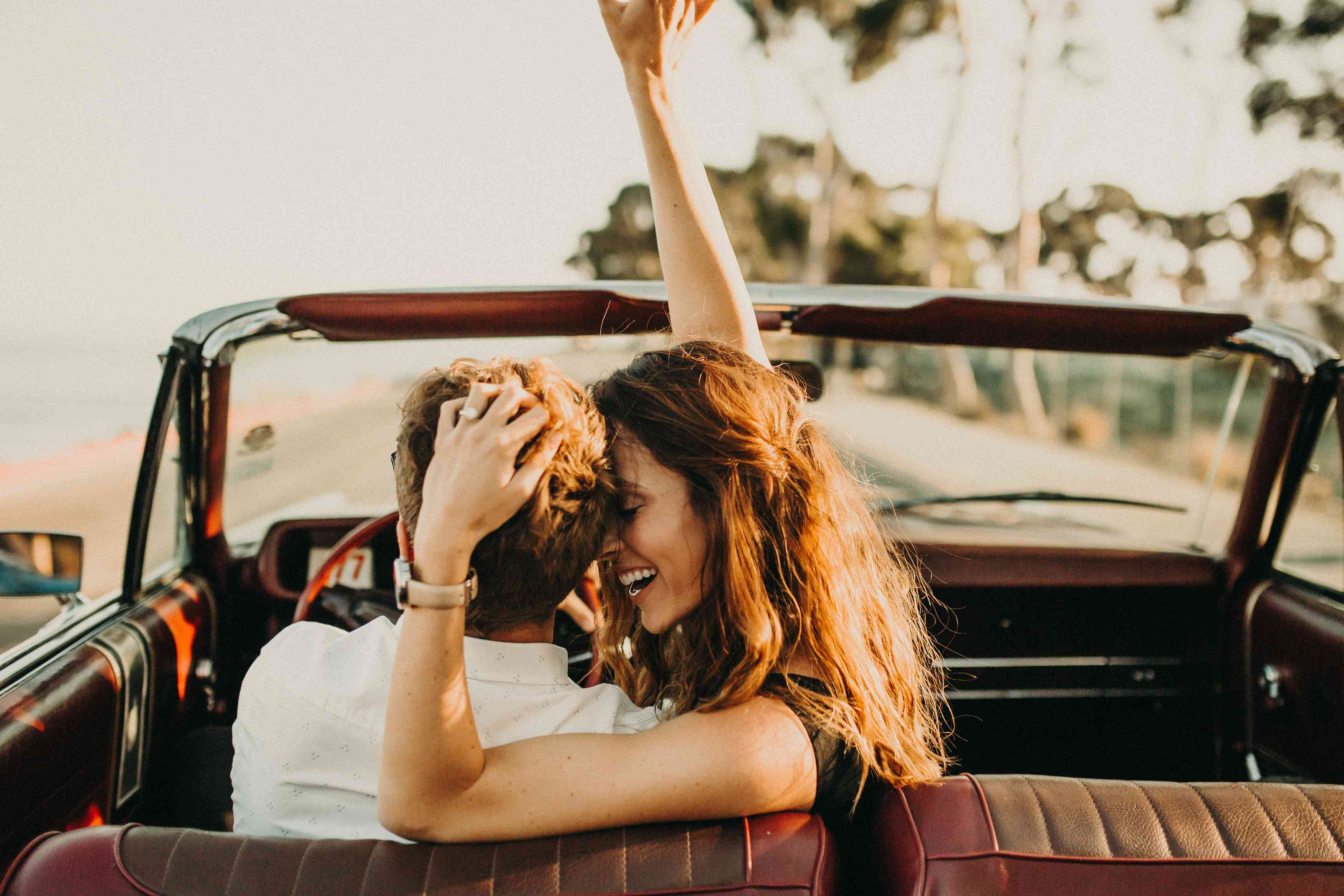 Couple in convertible driving into the sunset