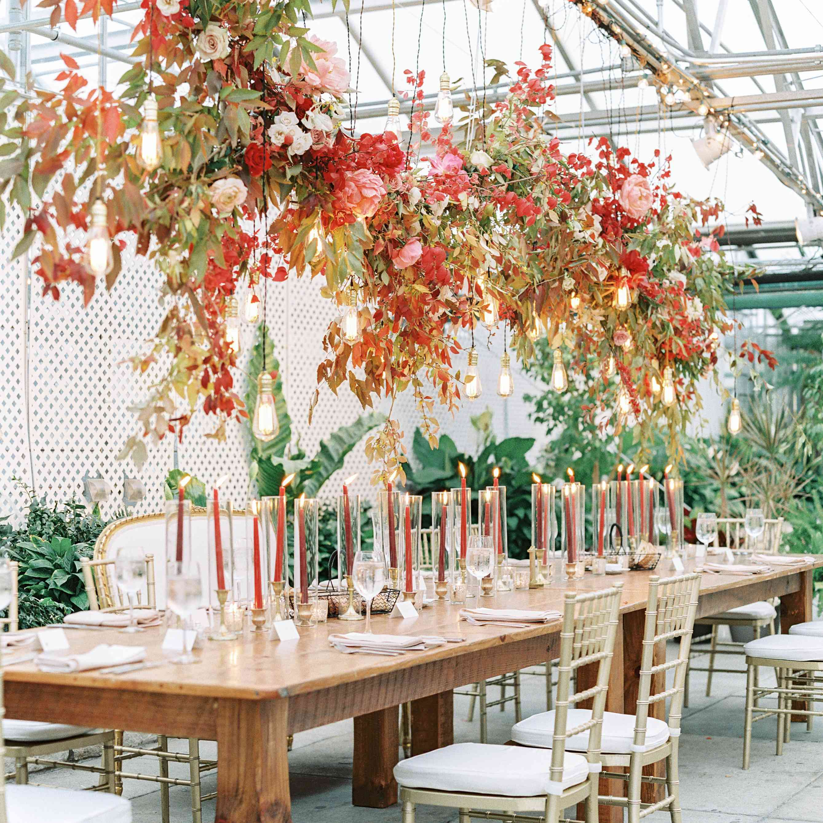 Floral and light bulb installation above wedding reception seating